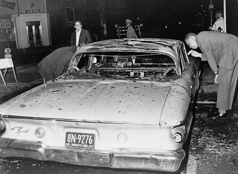 Detective examines burned out police car following rioting. Bedford-Stuyvesant, Brooklyn, 1964. (Stanley Wolfson / Library of Congress)