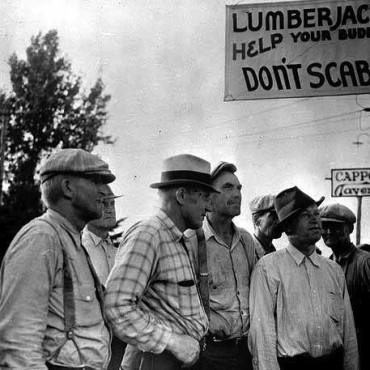Michigan timber workers reading the bulletin board at strike headquarters in 1937.