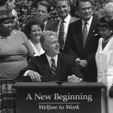 Bill Clinton prepares to sign the welfare reform bill into law in 1996.