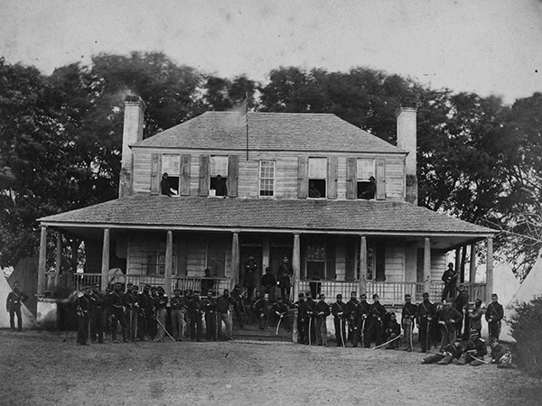 Union soldiers of the First Massachusetts Cavalry posed in front of plantation house on Edisto Island, South Carolina.