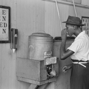 """A man drinks from a """"colored"""" water cooler in an Oklahoma City streetcar terminal (1939). Russell Lee / Library of Congress"""