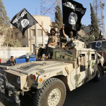 Members loyal to ISIS wave their flag during a parade in June 2014. Reuters