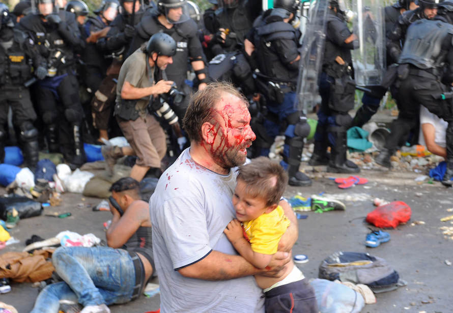 An injured migrant carries a child during clashes with Hungarian riot police at Serbian border last September. Karnok Csaba / Reuters
