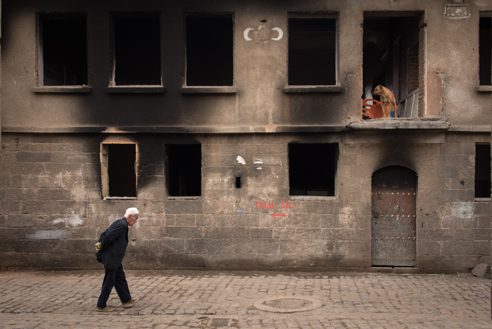 An elderly man walks in front of a burned-out buildings in Diyarbakir's Sur district.