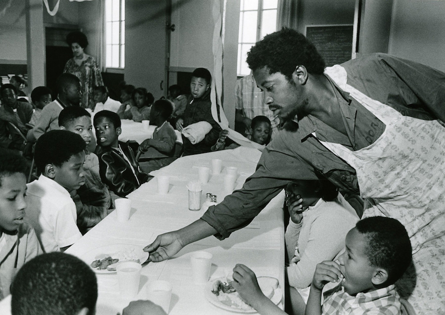 Charles Bursey hands a plate of food to a child as part of the Black Panther Party's free breakfast program. Photo courtesy of Pirkle Jones and Ruth-Marion Baruch